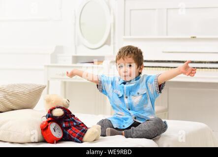 Kind im Schlafzimmer Märchen erzählen für Spielzeug. Märchen Konzept. Kid, Plüschbär in der Nähe von Kissen und Wecker, luxuriöse Innenausstattung Hintergrund. Junge mit f - Stockfoto