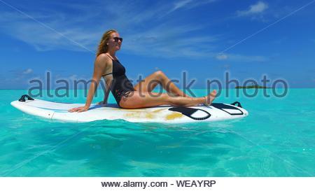 Lächelnden jungen Bikini Frau sitzt auf der Paddleboard im Meer - Stockfoto