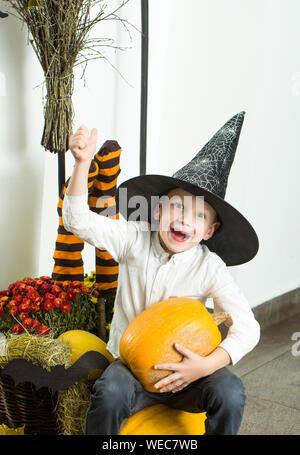 Halloween kleine Junge im Spinnennetz hat bei Socken. Halloween Kind mit glücklichen Gesicht. Urlaub und Feiern. Kind mit orange Kürbis in Hexenhut - Stockfoto
