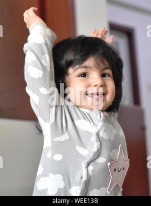 Happy Baby Mädchen lernen, wie man stand: entwicklungsmeilensteine - Stockfoto