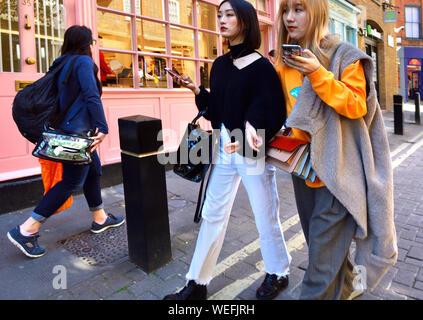 London, England, UK. Zwei junge japanische Frauen mit Mobiltelefonen - Stockfoto