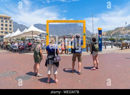 Touristen posieren für Fotos vor der Tafelberg, der V&A Waterfront, Cape Town, Western Cape, Südafrika - Stockfoto
