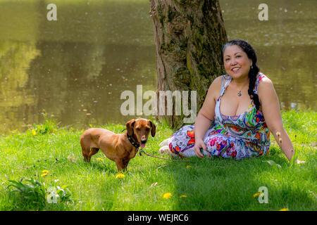 Happy mexikanische Frau sitzt im Gras mit ihrem Dackel von einem See umgeben von Bäumen in einem weißen Kleid mit bunten Dekoration umgeben - Stockfoto