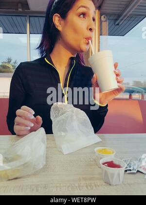 Junge Frau in Milchshake im Cafe - Stockfoto