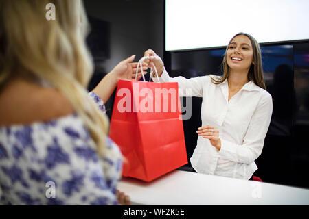 Blond Kunde erhält ihre poppigen Einkäufe von lächelnde Verkäuferin über einen Zähler