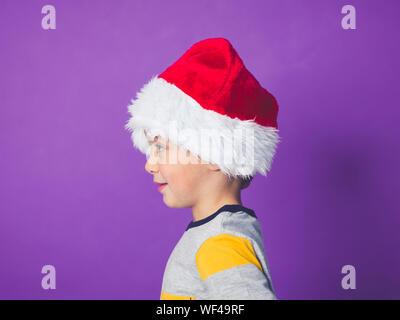 Junger Mann, Santa Hut gegen lila Hintergrund - Stockfoto