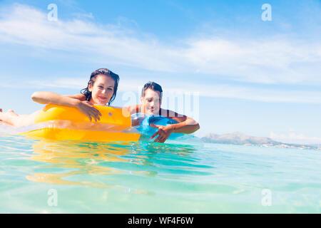 Porträt eines jungen Paares schwimmende aufblasbare Flöße im Meer gegen Sky - Stockfoto