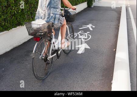 Niedrige Abschnitt von Frau Reiten Fahrrad auf dem Bürgersteig - Stockfoto