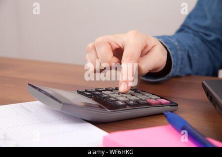 7/8 Hand mit Taschenrechner über Tabelle - Stockfoto