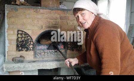 Portrait von Frau Brot backen im Ofen - Stockfoto