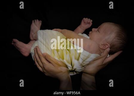 Doppelt belichtete Bild von Hand mit Baby und Blüten auf schwarzem Hintergrund - Stockfoto