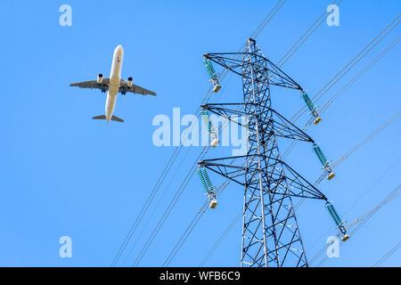 Ansicht von unten der ein Flugzeug im Landeanflug über eine Hochspannungsleitung gegen den blauen Himmel mit einem Strom Pylon im Vordergrund fliegen.