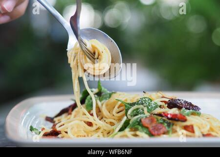 Gabel Twirls Spaghetti Nudeln in Löffel über Platte - Stockfoto