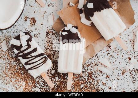 Drei coconut Yoghurt und Schokolade Eis am Stiel auf einem Tisch - Stockfoto