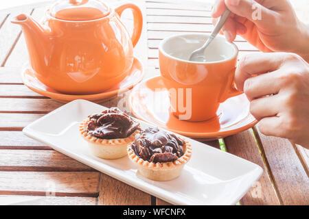 7/8 Hand von Frau rühren Kaffee in der Tasse von Tart und Teekanne serviert am Tisch - Stockfoto