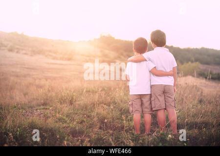 Ansicht der Rückseite des Geschwister stehen auf Feld - Stockfoto