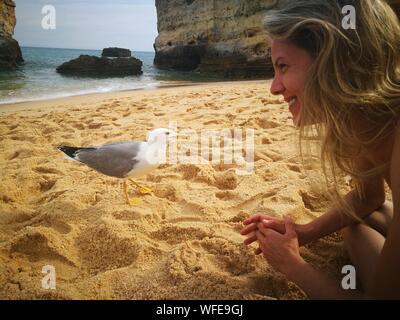 Junge Frau auf Seagull Hocken auf Sand an der Praia De Sao Rafael - Stockfoto