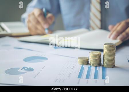 Close-up des Menschen schreiben In Tagebuch von Graphen und Stapel von Münzen auf Schreibtisch - Stockfoto