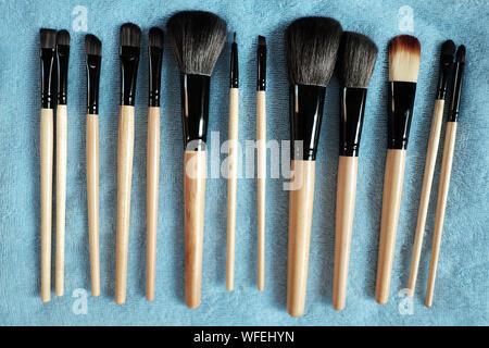 Direkt über der verschiedenen Make-up Pinsel über Textilwaren Stockfoto