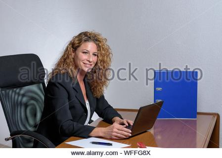 Freundlichen stilvolle junge Geschäftsfrau mit einem schönen Lächeln sitzen arbeiten an ihrem Schreibtisch im Büro anhalten, um in die Kamera blickt - Stockfoto