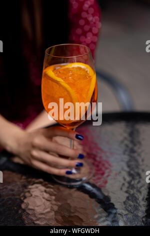 Frau sitzt an einem Tisch mit einem Aperol Spritz cocktail - Stockfoto
