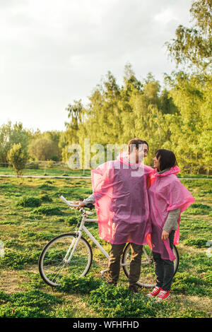 Junges Paar in Rosa Regenmantel mit Fahrrad auf Feld gegen Sky - Stockfoto