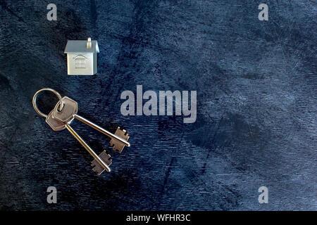 Ein paar Tasten liegen auf einem Vintage dunklen Hintergrund zusammen mit einer Imitation des Hauses in Form einer Metall Layout. Das Konzept der Verkaufsangebote - Stockfoto