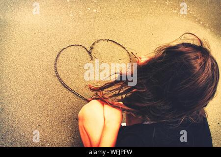 Ansicht der Rückseite Frau, die Herzform auf Sand am Strand - Stockfoto
