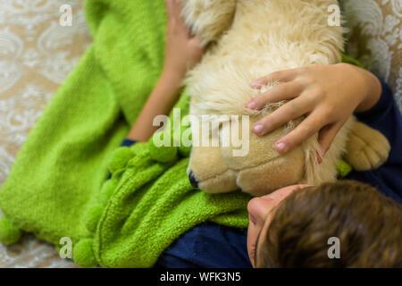 Junge Entspannen mit Spielzeug im Bett - Stockfoto