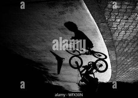Schatten der Junge Reiten Fahrrad auf der Straße - Stockfoto