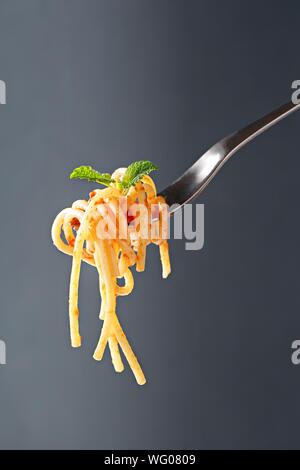Close-up von Spaghetti auf Gabel über grauer Hintergrund - Stockfoto