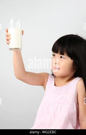 In der Nähe von Mädchen trinken Milch gegen Rosa Hintergrund - Stockfoto