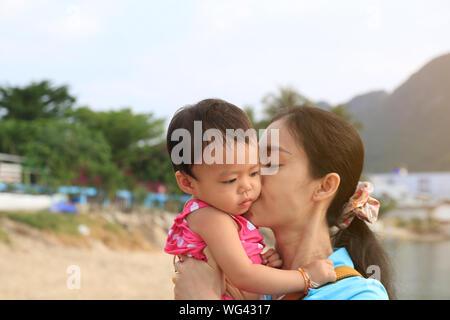 Nahaufnahme der Mutter küssen Tochter gegen den klaren Himmel - Stockfoto