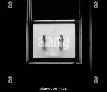Silhouette der Hände auf Milchglasfenster - Stockfoto