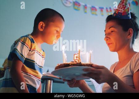 Boy Blasen Geburtstag Kerzen mit der Mutter zu Hause - Stockfoto