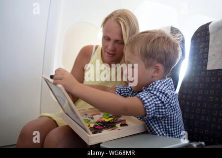 Mutter und Sohn spielen mit Spielzeug beim Sitzen im Flugzeug - Stockfoto