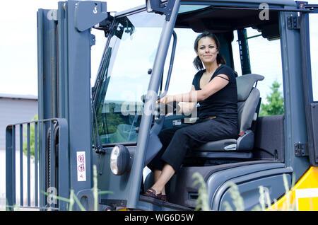Portrait von glücklichen Frau sitzt im Stapler - Stockfoto