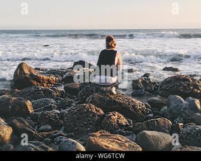 Volle Länge Rückansicht Frau hockend auf felsigen Küste gegen Himmel bei Sonnenuntergang - Stockfoto