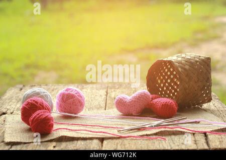 Schönheit rote Herzen und rosa Herz in Korb auf Holz-, Spool Strickgarn für Handarbeiten. - Stockfoto