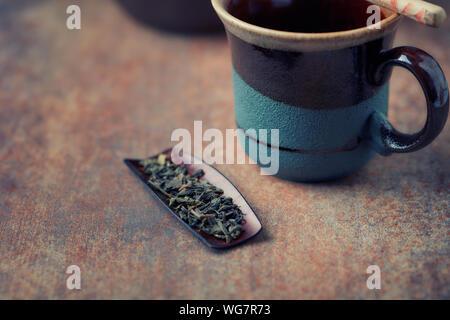 Trocken grüne Teeblätter auf rustikalen Hintergrund. Close Up. Kopieren Sie Platz. - Stockfoto