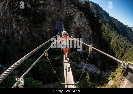 Eine Frau steigt der Klettersteig über Lac de la Rosière in der Nähe der Französischen Courchevel in den Alpen im Sommer. Die rope bridge.