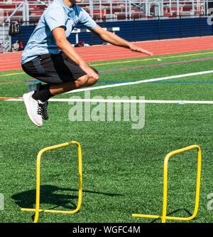 Ein High School runner ist das Springen über Gelbe Mini Hürden Cross Training für Kraft und coordinatiion während der Praxis auf einem Rasenfeld. - Stockfoto