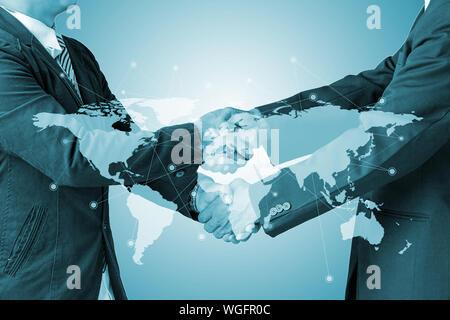 Close-up Männer Handshake vor blauem Hintergrund - Stockfoto