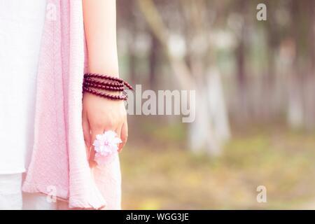 Zugeschnittenes Bild der Frau mit rosa Blüten - Stockfoto