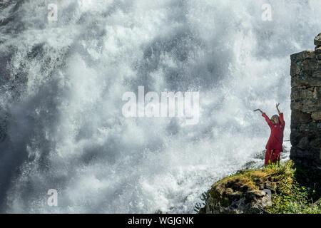 Rot gekleidete Frau ist eine Huldra, Märchen, Saga, Wasserfall Kjosfossen, Wasserfall in der Nähe von Fureberget, Tänzerin im roten Kleid, Felswände, Flåm, Sogn og Fjo - Stockfoto