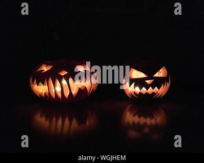 Beleuchtete Jack O Laternen am Tisch in der Dunkelkammer während der Halloween - Stockfoto