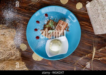 Eis und Kuchen auf einem blauen Platte auf einem braunen Holz- Hintergrund - Stockfoto