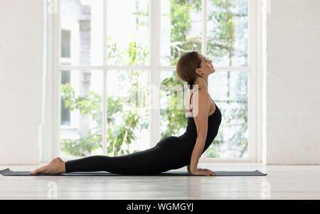 Schöne Frau Üben Yoga, Kobra, Bhujangasana Übung - Stockfoto