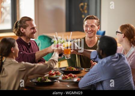 In warmen Farbtönen Portrait von Freunden anstoßen beim Sitzen am Tisch im Cafe genießen Sie erfrischende Getränke kalt, kopieren Raum - Stockfoto