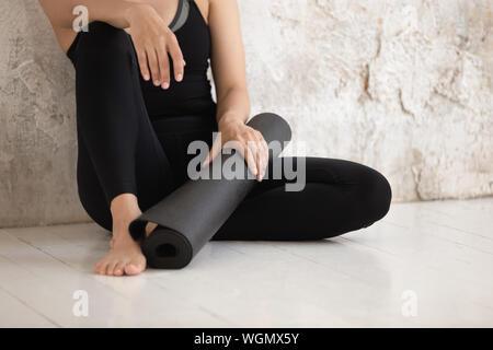 Junge Frau, Fitness Instructor holding Yoga Matte, sitzend auf dem Boden - Stockfoto